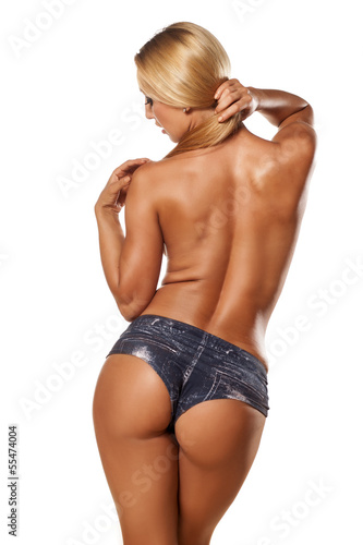 Rear view of pretty and muscular topless girl with blond hair