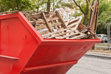 Grosser roter Container aus Metall mit Holz-Abfall