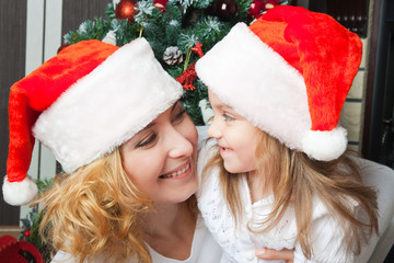 Happy mother and daughter in santa hats