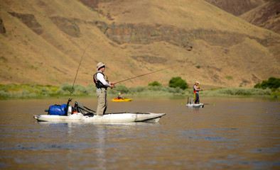 Men fishing on a river in kayaks