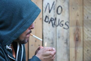 """Mann mit Zigarette, """"no drugs"""" im Hintergrund"""