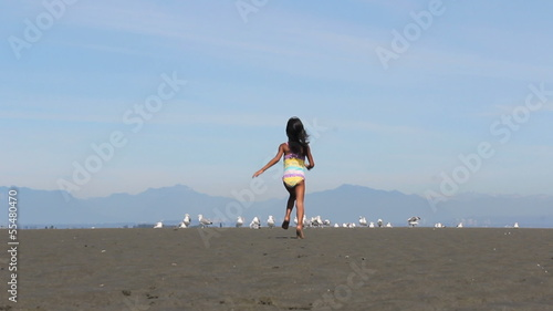Asian Girl Chasing Down Birds On The Beach