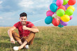 casual man sitting on the grass with balloons