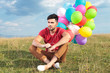 seated casual man with balloons looks away