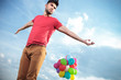 casual man with balloons looks to his side