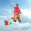 casual man with balloons jumps in the air