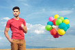 casual man with balloons holds hand in pocket