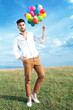 casual man with balloons and hand in pocket