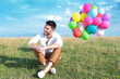 casual man with balloons sits on grass and smiles