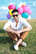 seated casual man with balloons and sunglasses