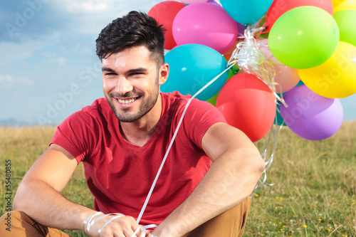 closeup of seated casual man with balloons