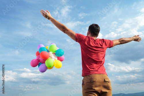 rear view of casual man with balloons