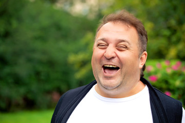 Handsome overweight man smiling and relaxing  outdoor
