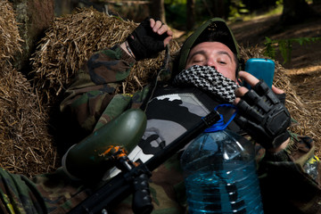 Paintball player resting and looking at the phone