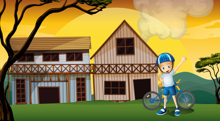 A female biker in front of the two wooden farmhouses