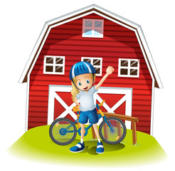 A female biker standing in front of the red barnhouse