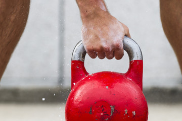 man picking up a kettle bell used for crossfit