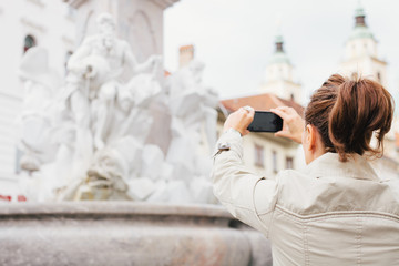 Woman / tourist taking photos of a monument with mobile phone