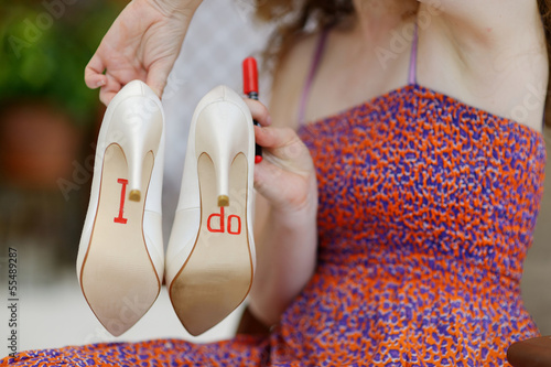 Bridesmaid displaying bride's shoes