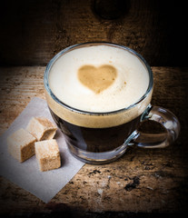 Coffee in glass with heart  foam and cane sugar on old wooden ba