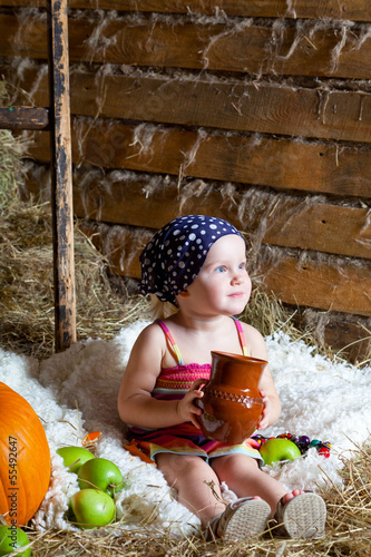 little girl sits on a mow with a milk jug