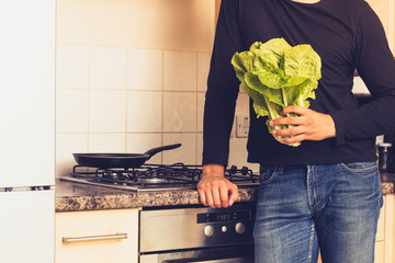 Man with head of lettuce in kitchen