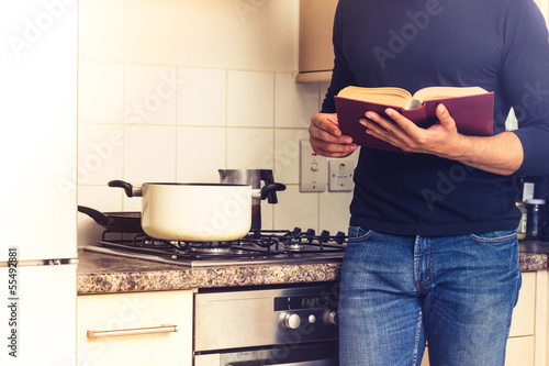Man reading big cook book in kitchen