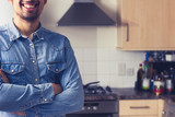Happy young man in tidy kitchen