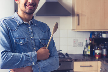 Happy young man with wooden spoon in kitchen