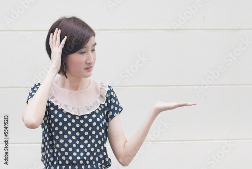 Asian young woman with headache showing product or text