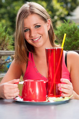 Attractive young woman drinking ice tea outdoor