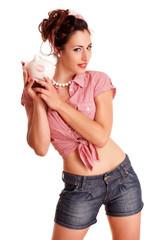 Mädchen hält Sparschwein mit Kussmund
