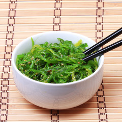 Seaweed with sesame seeds with chopsticks in bowl on bamboo mat