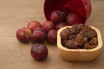 dried  and fresh  red plums on wooden background