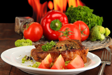 Piece of fried meat on plate on wooden table on fire background
