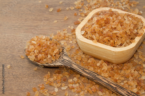 Organic rock candy sugar in wooden spoon