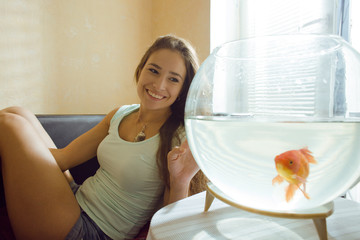 woman with goldfish at home, sunlight morning