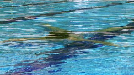 Beautiful woman swimming underwater coming out of swimmingpool
