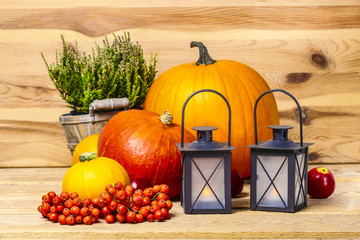 Black lanterns and orange pumpkins on wooden background