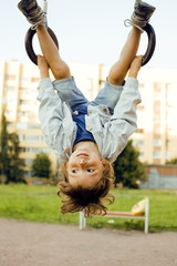 little cute boy hanging on playground