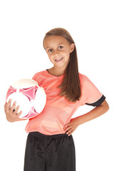 cute girl holding soccer ball on hips in pink jersey