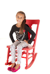 Young brunette girl sitting in pink rocking chair