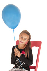 Brunette girl holding a blue balloon in a chair
