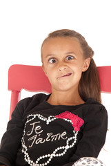 Girl in chair pulling a funny face in black shirt