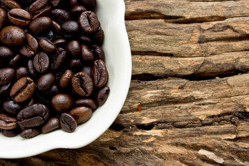 Coffee beans in white cup on wooden background.