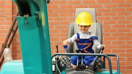 Cute boy as a excavator operator controls the levers