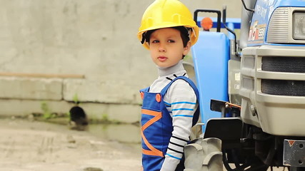 Cute boy in the role of worker stands near a tractor