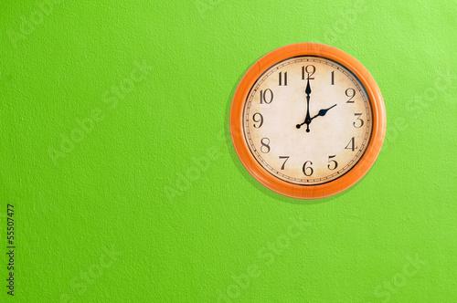 Leinwanddruck Bild Clock showing 2 o'clock on a green wall