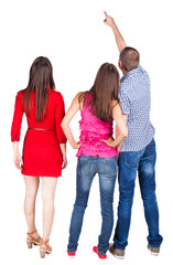 Back view of three friends. pointing man and two women looking.