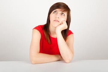 Die junge Frau sitzt gelangweilt an einem Tisch
